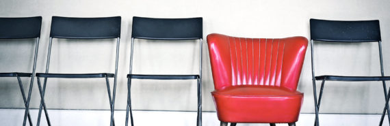 one red chair in group of black chairs
