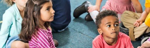 preschoolers sit on rug