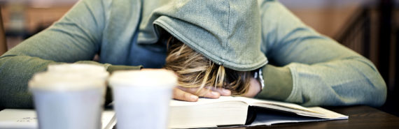 student sleeping on books on library desk