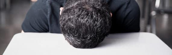 teen with head on classroom desk