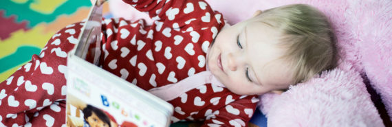 baby reading wearing a heart-covered onesie