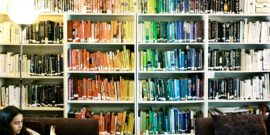 a bookshelf full of books organized by color