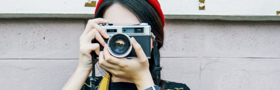 woman in red hat holds camera