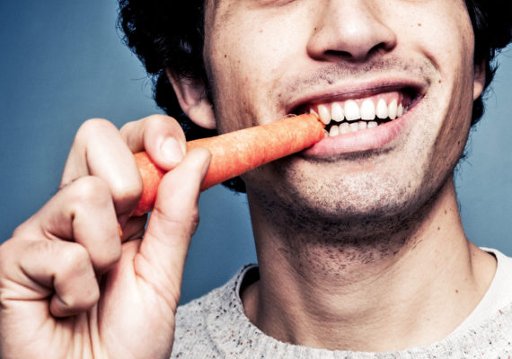 guy smiles while eating carrot