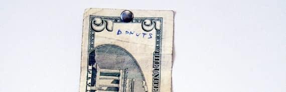 five dollar bill tacked to wall