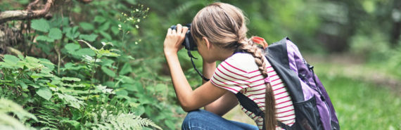 girl with backpack uses binoculars