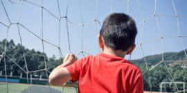 kid looks through soccer goal net