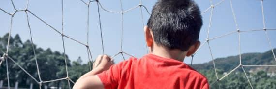 kid looks through soccer goal net