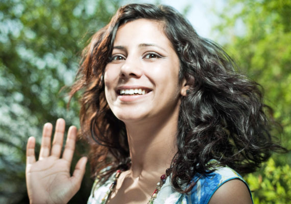 woman nervously waves hello