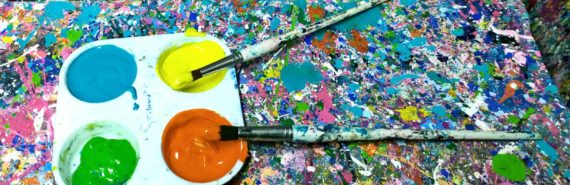 paintbrushes in paint on paint-covered table