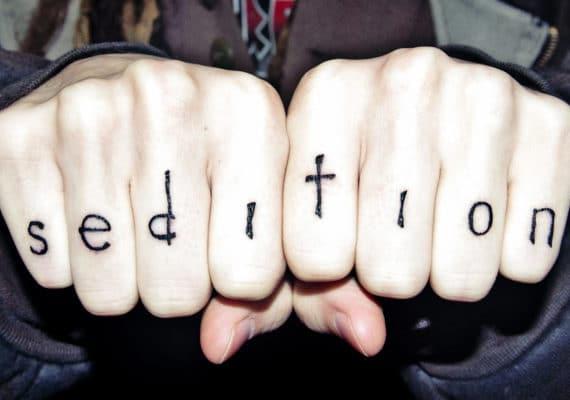 """knuckle tattoo says """"sedition"""""""