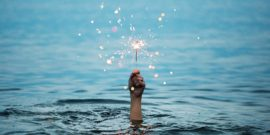 hand holds sparkler above water