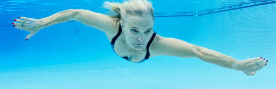 older woman swims under water