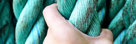 hand grasps teal rope