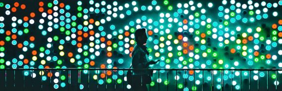 woman walking past colored lights