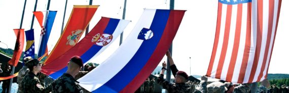 Soldiers raising NATO flags