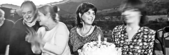 woman offers birthday cake in b/w