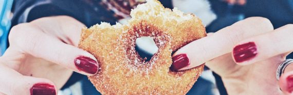hands with red nails hold doughnut