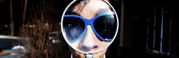 face in blue glasses behind magnifying glass