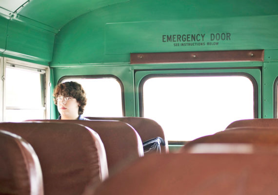 lone teen boy on school bus