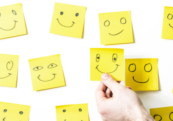 hand arranges yellow post-its with happy faces