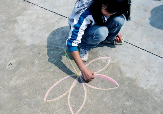 kid drawing with chalk on street