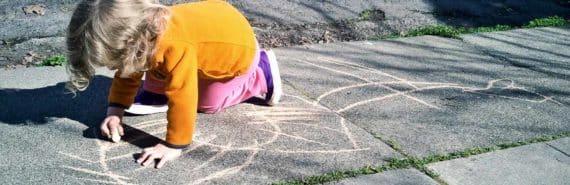 kid drawing on sidewalk with chalk