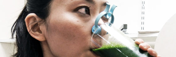 woman drinks green juice with nose clip