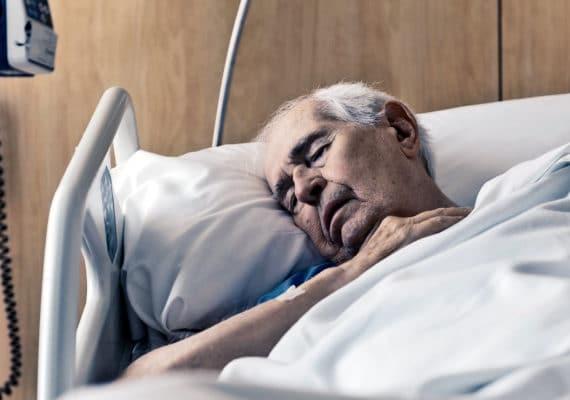 older man sleeping in hospital bed