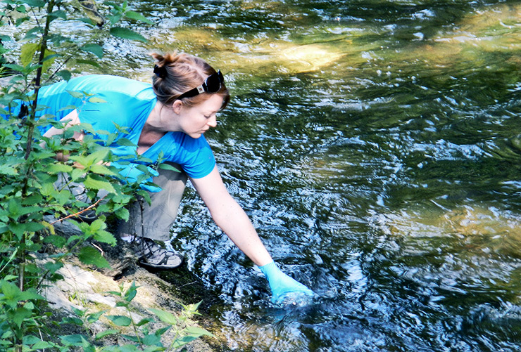 researcher grabs water sample for eDNA test