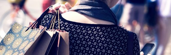 woman holding shopping bags over shoulder