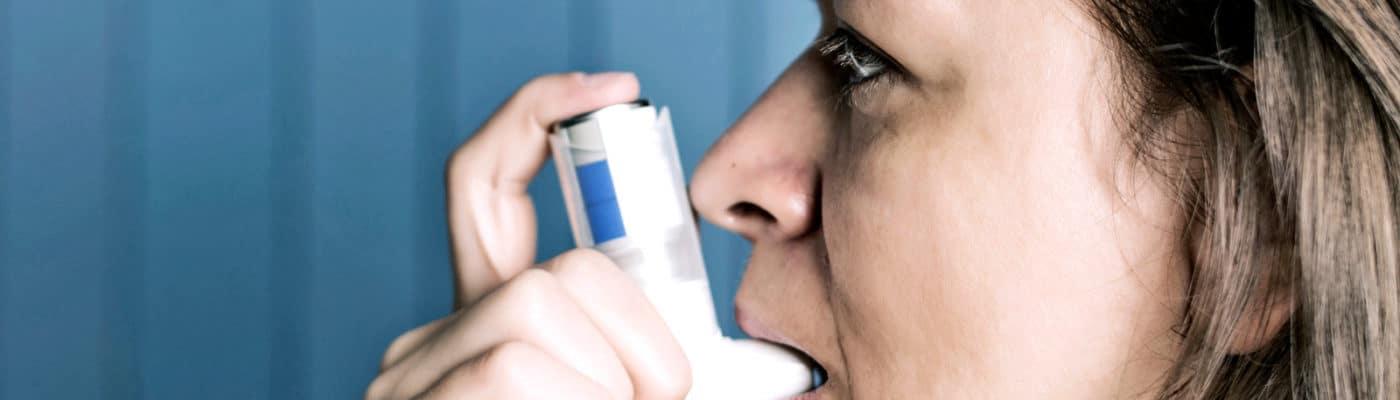 side portrait of woman using inhaler
