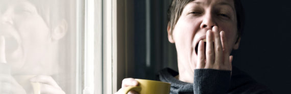 woman yawns and holds yellow mug