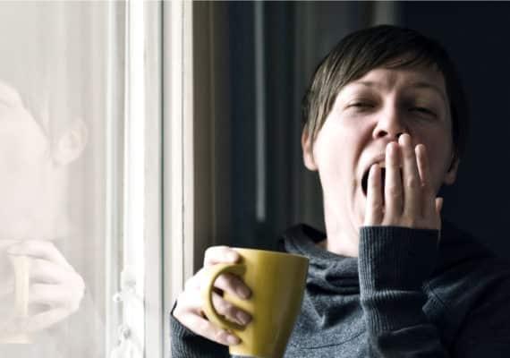 woman yawns and holds yellow mug