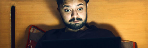 man watches a laptop in bed