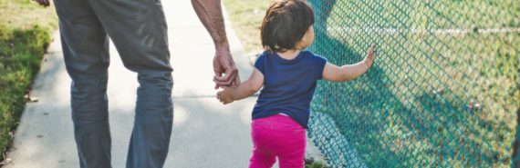 dad and toddler walk by fence