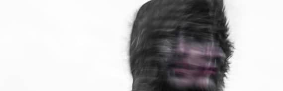 blurry face of woman wearing fur hood