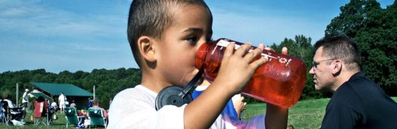 kid drinking water from plastic bottle