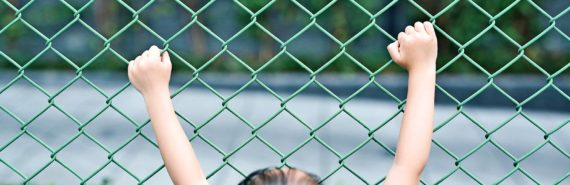 little girl holding fence