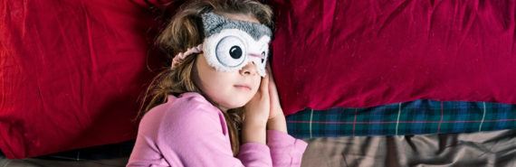 girl in owl sleep mask in bed