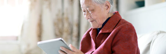 elderly woman uses tablet