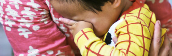 toddler hides face against mom