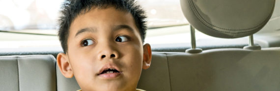 boy looks worried in backseat of car