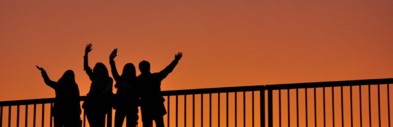people in silhouette wave on bridge - orange