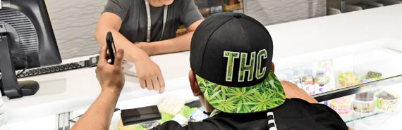 man in THC cap buys legal marijuana