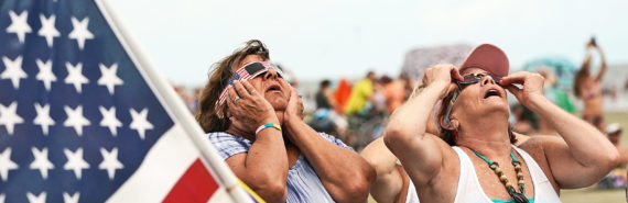 two women with flag watch solar eclipse