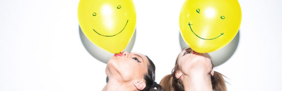 two women blow up yellow smiley balloons