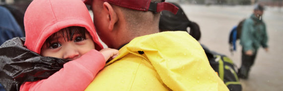 man carries toddler in pink hood in Hurricane Harvey flooding
