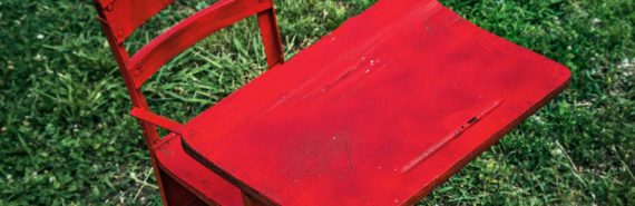 red school desk on grass