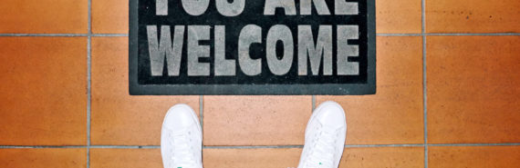 white sneakers and welcome mat